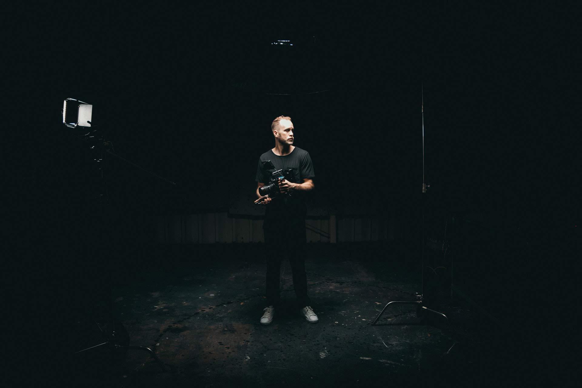 man-holding-videocamera-standing-in-studio-3379943