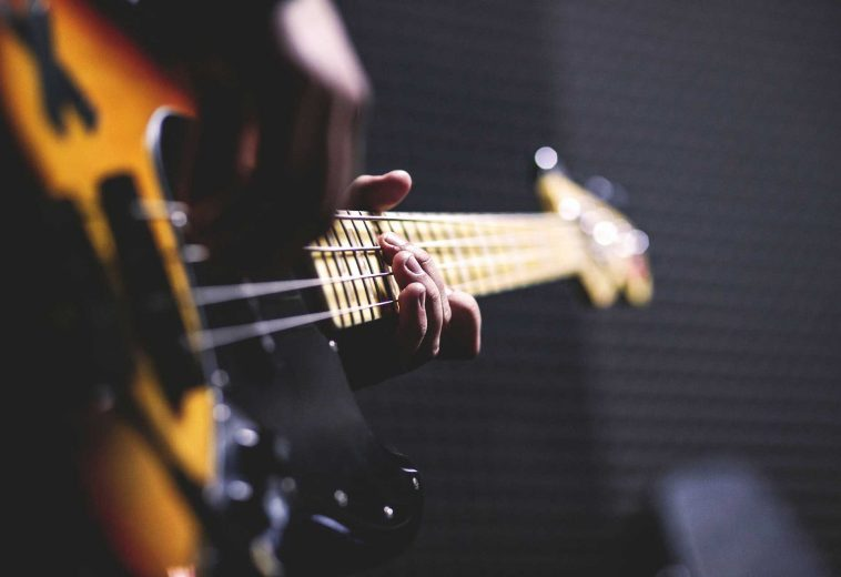 person-playing-sun-burst-electric-bass-guitar-in-bokeh-96380